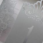 Ühtses stiilis kujundatud pulmakutse ja lauanumber.