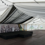 Suur telk koos väikse lava ja dekoratsioonidega.